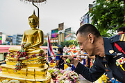 12 APRIL 2014 - BANGKOK, THAILAND: A Bangkok policeman prays and makes an offering to the Phra Buddha Sihing during the procession's stop in Thonburi. The Phra Buddha Sihing, a revered statue of the Buddha, is carried by truck through the streets of Bangkok so people can make offerings and bathe it in scented oils. Songkran is celebrated in Thailand as the traditional New Year's from 13 to 16 April. The date of the festival was originally set by astrological calculation, but it is now fixed. The traditional Thai New Year has been a national holiday since 1940, when Thailand moved the first day of the year to January 1. The first day of the holiday period is generally the most devout and many people go to temples to make merit and offer prayers for the new year.    PHOTO BY JACK KURTZ