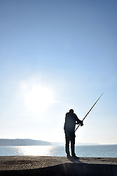 Man fishing on the sea wall Dieppe, France 2021