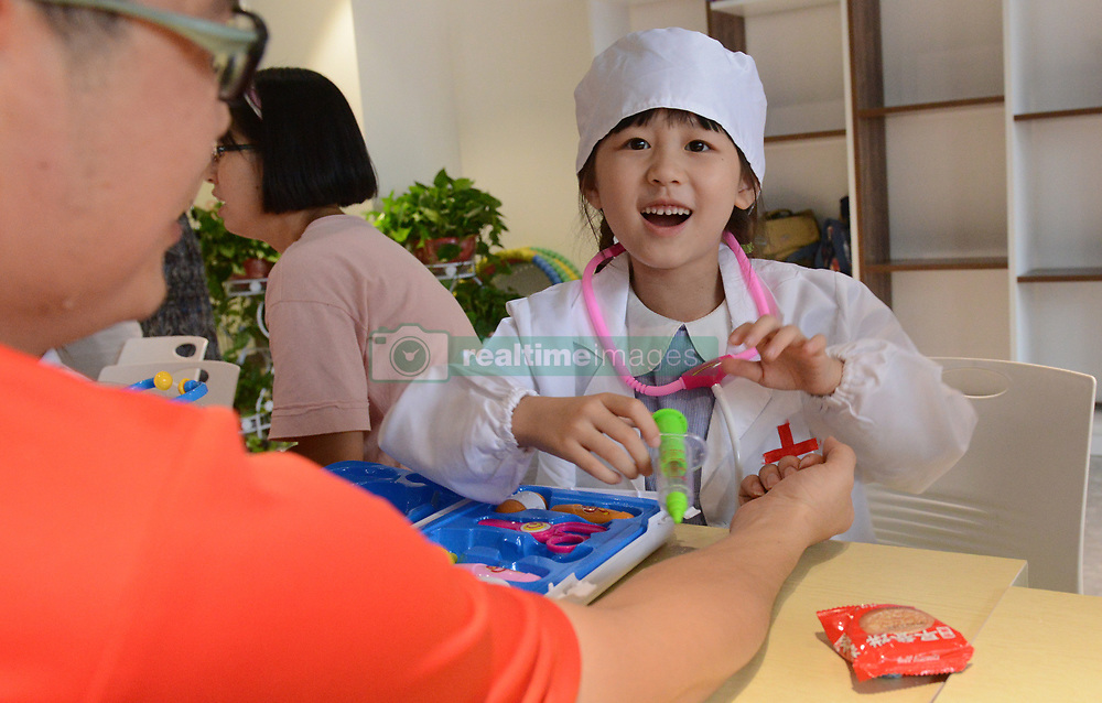 August 7, 2017 - Zhengzhou, Zhengzhou, China - Zhengzhou, CHINA-August 7 2017: (EDITORIAL USE ONLY. CHINA OUT) Kids in uniforms of doctor try to work as 'little doctors' at a hospital in Zhengzhou, central China's Henan Province, August 7th, 2017. (Credit Image: © SIPA Asia via ZUMA Wire)