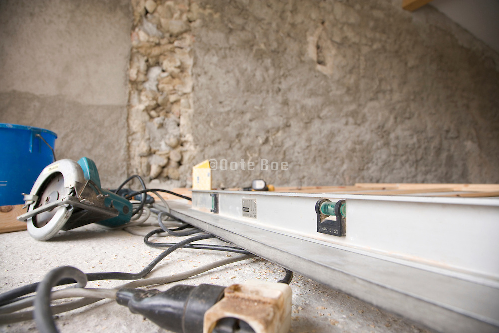 house being renovated with water level and a handheld circular saw