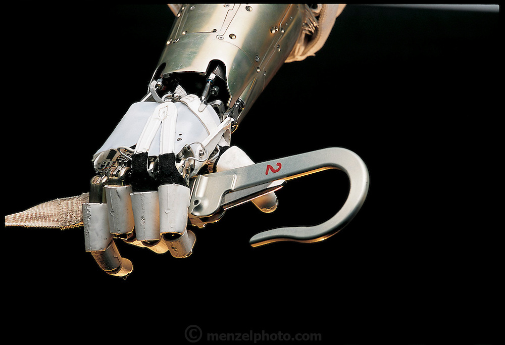 In a demonstration of mechanical dexterity, NASA's robot astronaut uses its hand to open a tether hook of the sort that will be used during the upcoming construction of the International Space Station. Designed to be as human-like as possible, Robonaut's hand has four fingers and an opposable thumb. Robonaut is the early prototype for the robotic astronaut being built at the Johnson Space Center in Texas. Intended to accompany astronauts into space, Robonaut will be especially important in emergencies. From the book Robo sapiens: Evolution of a New Species, page 131 top.