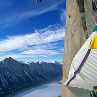 BAFFIN ISLAND, NUNAVUT, CANADA.  Alex Lowe (MR) climbs fixed rope above hanging bivouac on Great Sail Peak, Stewart Valley.