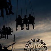 Fairgoers on a carnival ride are silhouetted against the setting sun on opening day of the State Fair of West Virginia at the State Fairgrounds in Fairlea, W.V. on Thursday, August 09, 2018.