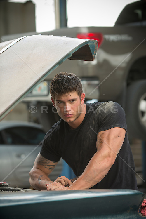 very good looking muscular auto mechanic with grease and dirt on his face