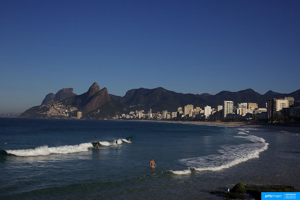 Early morning surfers at Ipanema beach catch a wave as the sunrise catches the light of the surrounding beachfront properties. Ipanema beach, Rio de Janeiro, Brazil. 12th July 2010. Photo Tim Clayton..The beaches of Rio de Janeiro, provide the ultimate playground for locals and tourists alike. Beach activity is in abundance as beach volley ball, football and a hybrid of the two, foot volley, are played day and night along the length and breadth of Rio's beaches. .Volleyball nets and football posts stretch along the cities coastline and are a hive of activity particularly at it's most famous beaches Copacabana and Ipanema. .The warm waters of the Atlantic Ocean provide the ideal conditions for a variety of water sports. Walkways along the edge of the beaches along with exercise stations and cycleways encourage sporting activity, even an outdoor gym is available at the Parque Do Arpoador overlooking the ocean. .On Sunday's the main roads along the beaches of Copacabana, Leblon and Ipanema are closed to traffic bringing out thousands of people of all ages to walk, run, jog, ride, skateboard and cycle more than 10 km of beachside roadway. .This sports mad city is about to become a worldwide sporting focus as they play host to the world's biggest sporting events with Brazil hosting the next Fifa World Cup in 2014 and Rio de Janeiro hosting the Olympic Games in 2016...