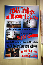 23 July 2010. Grand Isle, Louisiana. <br /> A sales poster pitched primarily to oil clean up workers as seen on the wall at the Grand Isle marina advertising FEMA trailers at discount prices. These would be the same FEMA trailers that are known to be contaminated with formaldehyde and are the subject of extensive legal wrangling following their use after hurricane Katrina. The FEMA trailers are known to have made people very sick. How is it possible for these trailers, effectively contaminated government owned stock to now be available through private dealers to the general public? <br /> BP's catastrophic oil spill in the Gulf of Mexico would appear to be encouraging additional contamination of clean up crews through private sales of contaminated FEMA trailers. How is this possible? <br /> Photo credit; Charlie Varley/varleypix.com