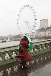 © Licensed to London News Pictures. 03/01/2016. London, UK. A woman with an umbrella struggles to walk during a gust of wind near the London Eye.  London and the UK has experienced heavy rain and wind today. Photo credit : Vickie Flores/LNP