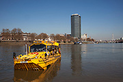 Scene along the River Thames as a Duwk amphibious vehicle drives out of the river onto dry land. The Duck Tours company. London