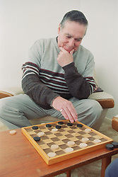 Elderly man with Alzheimer's disease playing game of draughts,
