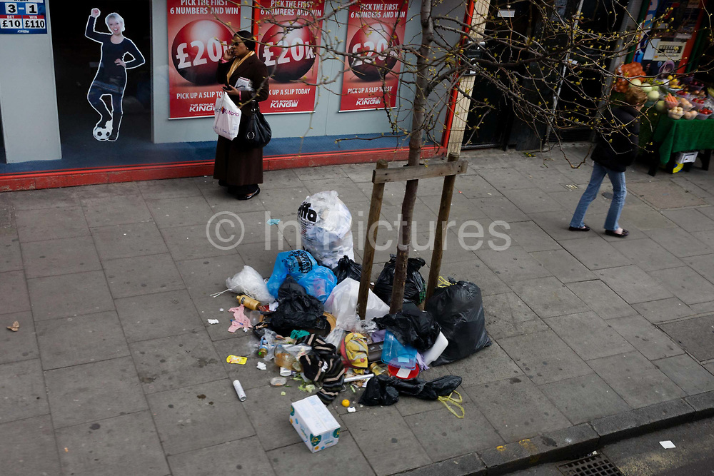 Londoners walk past the mess of litter and rubbish torn apart by overnight animals on a south London street in the borough of Lambeth. The garbage has been thrown under a sapling on this dirty pavement, outside a betting shop run by Betfred. Clothing, household items and foodstuffs are strewn across the sidewalk as pedestrians pass-by.