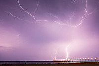 A long exposure shot reveals multiple lightning strikes over the lighthouse in South Haven, Michigan