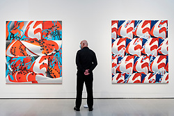 """© Licensed to London News Pictures. 07/09/2021. LONDON, UK. A staff member poses between (L to R) """"Echo Complex 2"""", and """"Imitation Complex"""", both 2021, by Vivien Zhang. Preview of 'Mixing It Up: Painting Today', a group new exhibition at the Hayward Gallery which highlights the UK's emergence as a vital international centre of contemporary painting with works by 31 artists on display.  The show runs 9 September to 12 December.  Photo credit: Stephen Chung/LNP"""