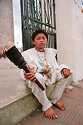 Portrait of young male pilgrim to the Basilica de Guadelupe seating holding flaming tourche, in front of Catedral de San Gervasio wearing Our Lady of Guadelupe shirt and rosary.