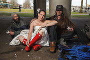 USA, Oregon, Portland. Tom McCall Waterfront Park, disgruntled bride, (actually divorced) with two homeless men. MR