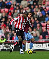 Photo: Andrew Unwin.<br />Sunderland v Aston Villa. The Barclays Premiership.<br />19/11/2005.<br />Aston Villa's Kevin Phillips (R) puts an arm around Sunderland's Justin Hoyte (L).