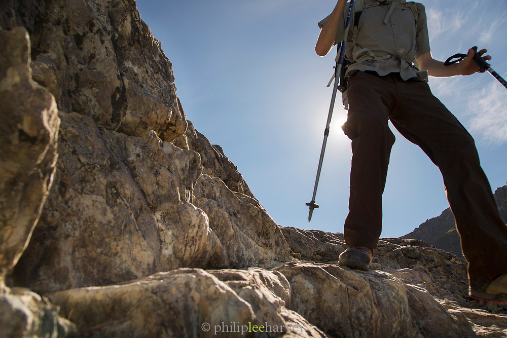 Low section view of a male hiker walking on rocks, Routeburn Track, South Island, New Zealand
