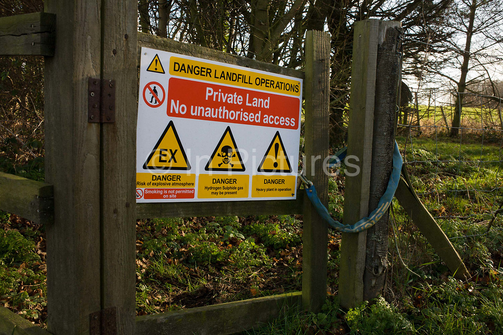 A sign warning passers-by of chemical and biological landfill dangers on property owned by Waste Management, Offham, Kent. The sign has been placed on a wooden fence on private land at the side of a village road in this rural area of southern England. A substantial lock has been placed through the fence and gate deterring those wishing to take a shortcut through to nearby woods. Places like Offham were chosen for London's rubbish and for many years gigantic ARC lorries left London for the villages in order to fill the quarries with metropolitan waste.
