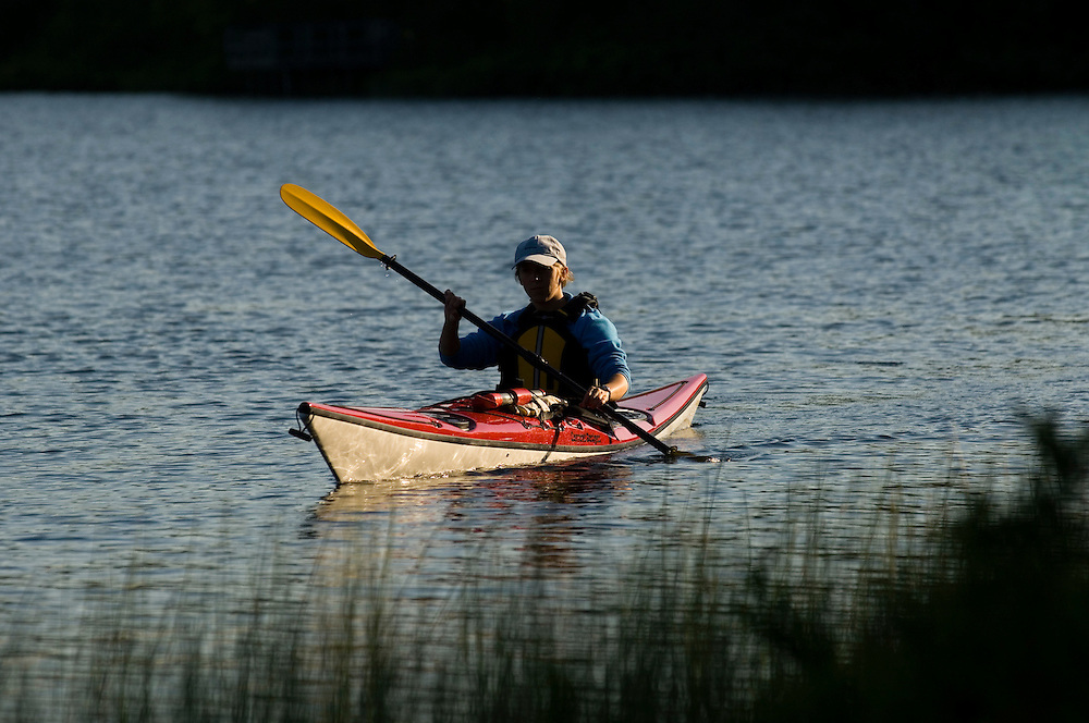 A female sea kayaker paddles a red kayak on Harlow Lake in the Escanaba River State Forest near Marquette Michigan.