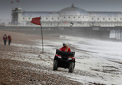 © Licensed to London News Pictures. 30/07/2021. Brighton, UK. Life guards patrol Brighton beach on a quad bike and on foot (L) as high wind whips up the waves. Parts of the south are feeling the effects of Storm Evert, the first named storm of summer 2021. Photo credit: Peter Macdiarmid/LNP