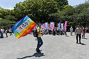 An anti nuclear protester carrying a rainbow flag at a protest in Shiba Park, Minato ward, Tokyo, Japan Sunday June 2nd 2013