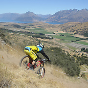 Adrian Main from Australia in action during the New Zealand South Island Downhill Cup Mountain Bike series held on The Remarkables face with a stunning backdrop of the Wakatipu Basin. 150 riders took part in the two day event. Queenstown, Otago, New Zealand. 9th January 2012. Photo Tim Clayton