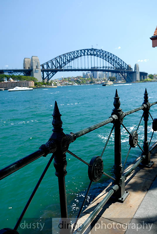 Detail of railing that completely encircles Circular Quay, with Sydney Harbour Bridge in background. Circular Quay, Sydney, Australia