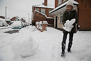 Girls having fun in Kings Heath in heavy snow fall building a snow man on Sunday 10th December 2017 in Birmingham, United Kingdom. Deep snow arrived in much of the UK, closing roads and making driving treacherous, while many people simply enjoyed the weather.