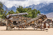 An antique wooden threshing machine is parked outdoors at the Eastern California Museum, 155 N. Grant Street, Independence, California, 93526, USA. The Sierra Nevada mountains loom in the background. The Museum was founded in 1928 and has been operated by the County of Inyo since 1968. The mission of the Museum is to collect, preserve, and interpret objects, photos and information related to the cultural and natural history of Inyo County and the Eastern Sierra, from Death Valley to Mono Lake.