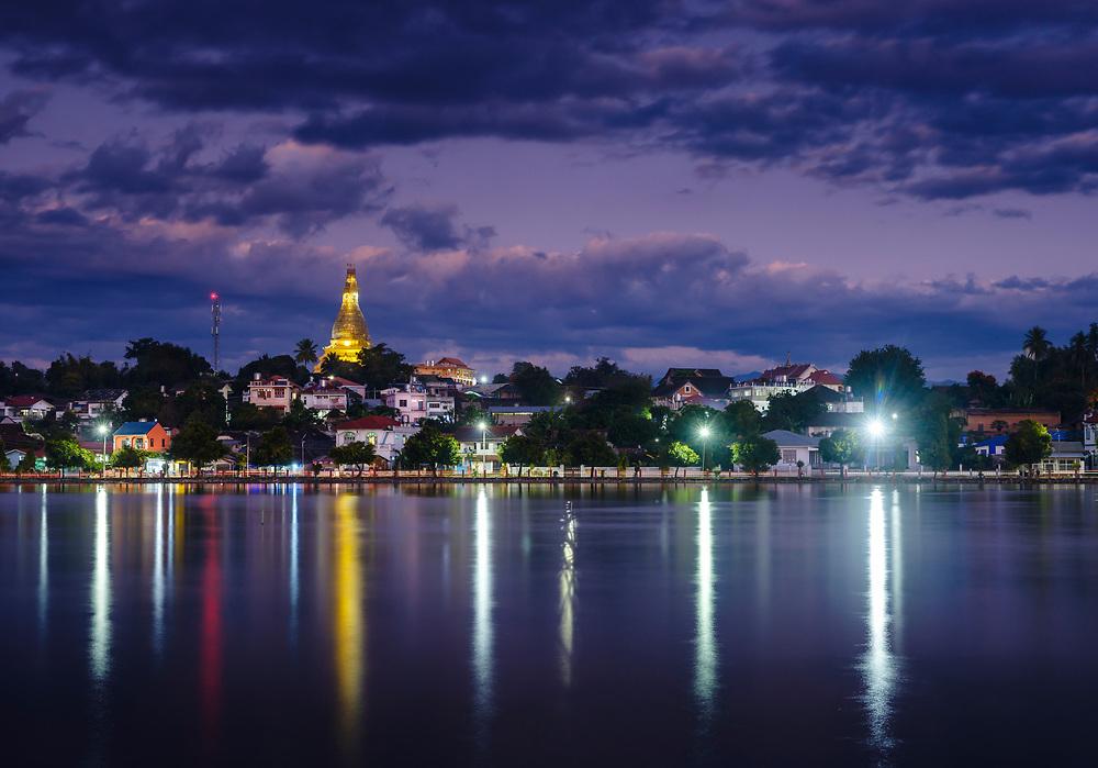 KYAING TONG, MYANMAR - CIRCA DECEMBER 2017:  View of lake Nong Tung and Wat Noi Naw in Kyaing Tong at night.