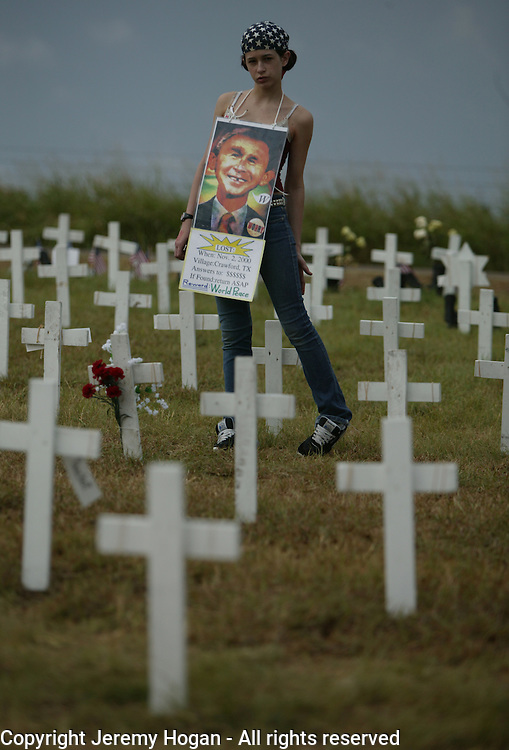 Danielle Lane of Dallas, Texas walks among hundreds of crosses at Camp Casey II during the Cindy Sheehan Vigil.