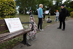 """© Licensed to London News Pictures. 16/05/2020. Manchester, UK. Demonstrators chat alongside a placard reading """" Hey Bill Gates Fuck you and your vaccine """" . An anti-lockdown, """"mass gathering"""" demonstration is held in Platt Fields Park in protest at government measures to control the spread of Covid-19. A group calling itself the UK Freedom Movement has organised a series of demonstrations across the UK. Photo credit: Joel Goodman/LNP"""