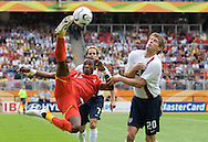 Ghana's John Pantsil (15) kicks the ball in the air, over the USA's Brian McBride (20) and Eddie Lewis (7). Ghana defeated the USA 2-1 in their FIFA World Cup Group E match at Franken-Stadion, Nuremberg, Germany, June 22, 2006. Ghana advances to round of 16 and the USA is out of the tournament.