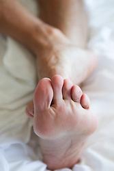 detail of a man's feet against a white sheet