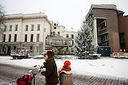 Een vrouw loopt met de fiets met haar kind achterop door de sneeuw bij het stadhuis van Utrecht. In grote delen van Nederland is vandaag voor het eerst sneeuw gevallen