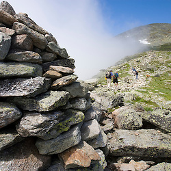 Hikers on the Lion Head Trail below the summit of Mount Washington.  Tuckerman  Ravine is below the fog.  New Hampshire's White Mountain National Forest.