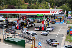 Licensed to London News Pictures. 25/09/2021. London, UK. Large queues<br /> form at an Esso petrol station on the A3 near Kingston, south-west London today as desperate motorists stop to fill up. Yesterday, petrol stations across London and the South East were on critical levels with many running out of fuel as oil giants struggle to maintain deliveries due to the lack of HGV drivers. Photo credit: Alex Lentati/LNP
