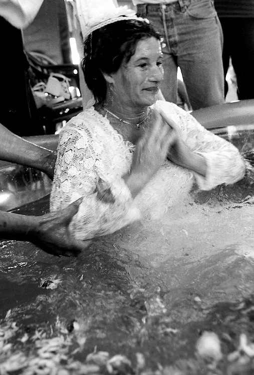"""Woman during the baptism. France, Marville, August 2002 - 40,000 Gypsies from all over the Europe come together and pray in Marville, a little village in France. They encamped in a former air base of NATO during 1 week. """"Vie et Lumiere"""" is an International Evangelic Community. ©Jean-Michel Clajot / Cosmos"""