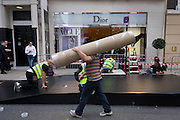 An outdoor set is constructed for the Christian Dior fashion house in London's Bond Street during Vogue's Fashion's Night Out festival in the streets of the West End. Contracted workmen wearing high-vis tabard vests put the finishing touches to a raised ramp that a Dior-sponsored taxi cab will be placed upon, complete with fake double-yellow lines. The fake road surface is being laid out as other workmen prepare a Dior street sign and staple parts of the ramp together.