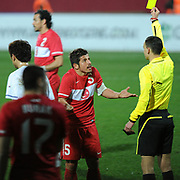 Referee's Sergii BOIKO (R) show the yellow card to Turkey's Emre BELOZOGLU (C) during their International friendly soccer match Turkey between South Korean at the Avni Aker stadium in Trabzon, Turkey on Wednesday 09 February 2011. Photo by TURKPIX
