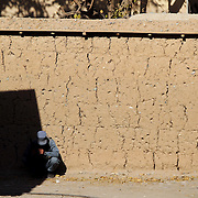 An Afghan National Police (ANP) officer guards a girl's school in the village of Nari, Kunar Province of Eastern Afghanistan during a water filter demonstration with Waves For Water and the US Military.