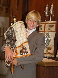 good looking blond Bar Mitzvah boy holding a Torah
