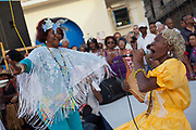 Female Cuban older elderly women singing and dancing wearing colourful costumes, performance in Havana old town, local dance and theatre group enacting the slave trade, colonial rule and how African religion and beliefs continuing, becoming what is now Santeria.