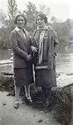 two women posing by water edge 1920s
