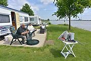 Nederland, Slijk-Ewijk, 3-6-2013Op camping De Grote Altena is men bezig de caravans die dicht aan het water staan te verplaatsten vanwege het verwachte hoogwater in de Waal. de heer Meijer uit Wierden bezig met demonteren van een tafeltje wat later een aanhangertje ingaat. De caravan wordt door de camping verplaatst.Foto: Flip Franssen/Hollandse Hoogte