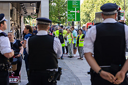 Police watch as Yellow Vest protesters gather outside Magistrates Court as PC Connor Pennery, 27, of the Met Police Territorial Support Group appears on assault charges that arose during a public order situation involving the right wing Yellow Vests in Jermyn Street, Piccadilly on Saturday February 16th, 2019. London, August 29 2019.