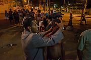 Crackland near Manguinhos shantytown. A member of evangelism team leads a pray together with a crack dependent.