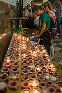 Inside the chapel where the icon of the Black Madonna of Czestochowa is shown, people ignite a candle to symbolize their prayer and write their intention on a piece of paper as confirmation, Poland 2018.