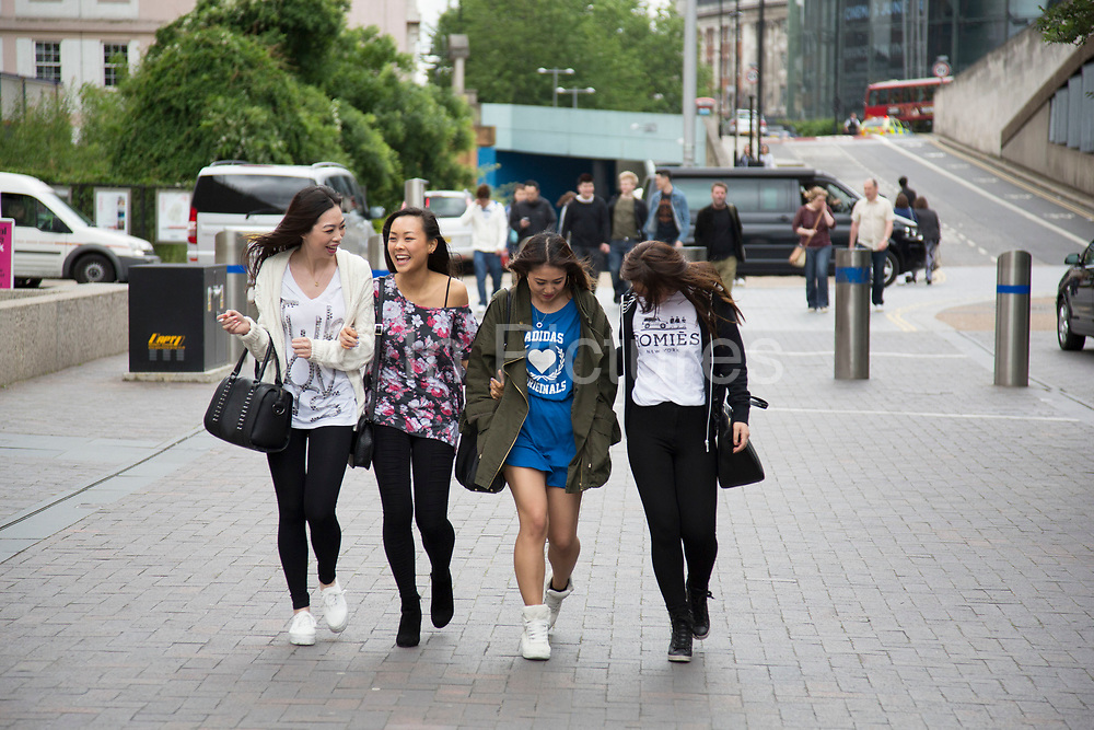 Four girls walk arm in arm laughing towards the Vietnam Open Festival 2013 (VOF 2013) is a Vietnamese cultural festival celebrating the very best of Vietnam in London. Held on the Southbank Riverside, the local diaspora mix with multi cultural Londoners.
