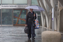 © Licensed to London News Pictures.  09/09/2021. Edinburgh, Scotland. A woman takes shelter from the rain underneath an umbrella in front of the Scottish Parliament in Edinburgh. Scotland is currently the Covid capital of the UK with 17 out of 20 hotspots north of the border. Photo credit: Marcin Nowak/LNP