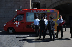 © LONDON NEWS PICTURES 2011. Photo by Paul Treacy. Men in suits gather at an ice cream van on the warmest day of the year so far in London.